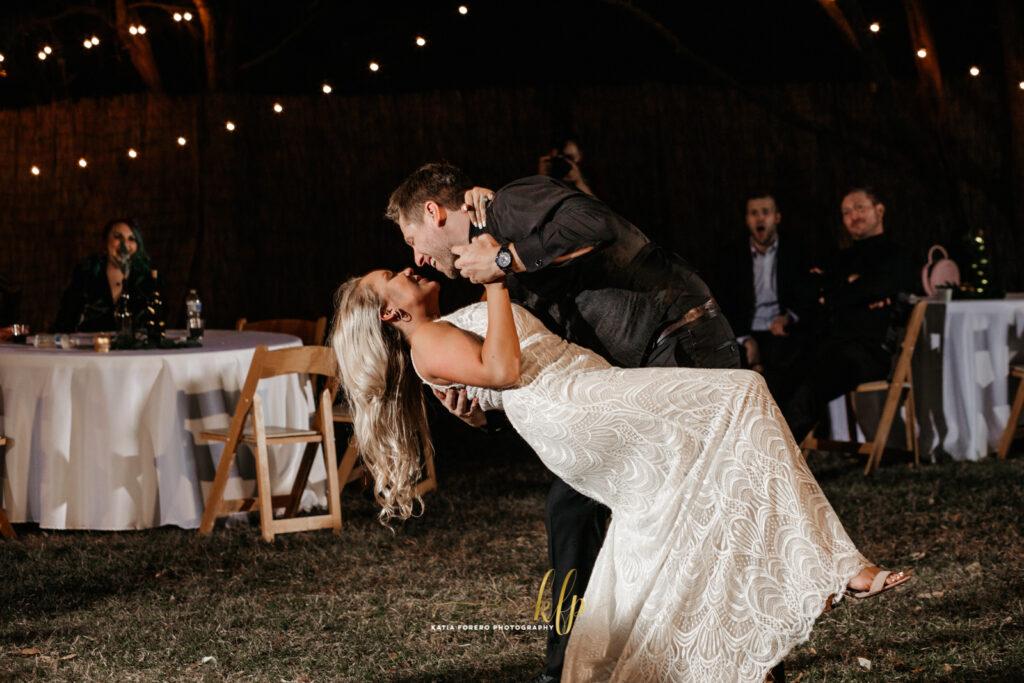 groom dips his wife in outdoor wedding reception